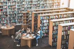 Glad students studying in athenaeum. Satisfied male and positive girls reading books while situating at table in library. A lot of books locating on shelves Royalty Free Stock Images