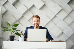 Satisfied male using computer in office. Waist up portrait of smiling businessman working at laptop in personal cabinet. He is sitting at desktop with confident Stock Image