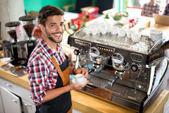 Satisfied male waiter holding cup. Hot coffee Stock Images