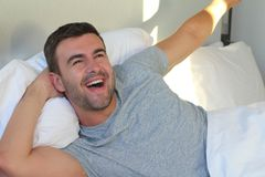 Satisfied male waking up with positivity.  stock image