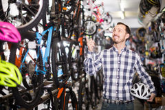 Satisfied man in bicycle shop chooses for himself sports bike Royalty Free Stock Photography