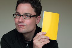 Satisfied man with dark glasses holding a blank paper for advertising Royalty Free Stock Images