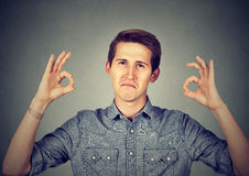 Satisfied man gesturing Ok sign Royalty Free Stock Photography