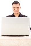 Satisfied man with glasses in a black shirt looking at laptop Stock Photos
