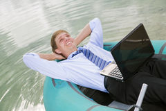 Satisfied man lay in boat and smile Royalty Free Stock Photos