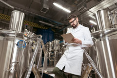 Satisfied man making notes at beer factory Royalty Free Stock Images