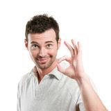 Satisfied man with okay sign. Satisfied young man showing okay sign isolated on white background Royalty Free Stock Image