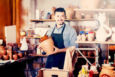 Satisfied man potter holding ceramic vessels. In atelier royalty free stock photos