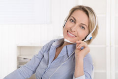 Satisfied mature businesswoman with headphone at office. Stock Image