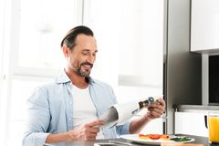 Satisfied mature man reading newspaper. While having tasty breakfast at the kitchen table stock photography
