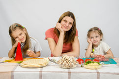 Satisfied mother with two daughters sitting resting his head in his hands at the table with products for pizza Stock Photography