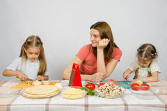 Satisfied mother watching her little daughter to help her cut products at kitchen table Royalty Free Stock Photo