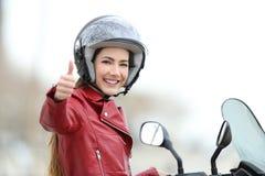 Satisfied motorbiker gesturing thumbs up. On her motorcycle outdoors Royalty Free Stock Image