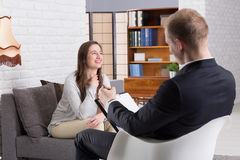 Satisfied with my actual life. Smiled women talking with her men psychologist in therapy center Royalty Free Stock Photo