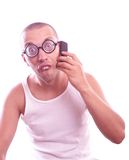 Satisfied nerd in eyeglasses calls by mobile phone Royalty Free Stock Photos
