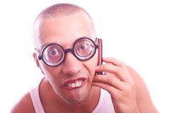 Satisfied nerd in eyeglasses calls by mobile phone Stock Photos