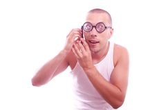 Satisfied nerd in eyeglasses calls by mobile phone Royalty Free Stock Photo