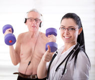 Satisfied nurse with senior man rehabilitation Royalty Free Stock Image
