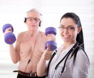 Satisfied nurse with senior man rehabilitation Royalty Free Stock Image