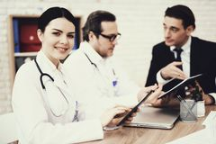 Satisfied nurse typing on tablet in medical office. Blurred doctor and patient in background. stock photo