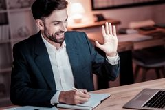 Satisfied occupied man having video conversation and writing. Stock Photo
