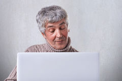 A satisfied old male having conversation online on his laptop while siting at home. An attractive mature man browsing internet usi Royalty Free Stock Photos