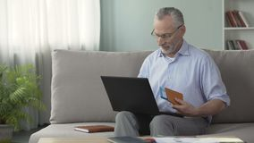 Satisfied old man booking hotel room on laptop, holding passport and tickets. Stock footage stock video