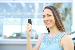 Car owner showing keys after buy. Satisfied owner showing keys after buy in a car dealership Royalty Free Stock Images