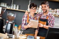 Satisfied owners look orders coffee shop Stock Image