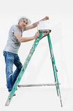 Satisfied painter. Smiling painter on a ladder Royalty Free Stock Photo