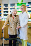 Satisfied pharmacy customer with pharmacist. Satisfied elderly customer in brown jacket using walker and holding hands with friendly young blond female stock photography