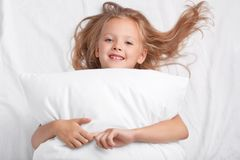 Satisfied playful girl with charming smile, embraces pillow, lies on white pillow, has good rest, enjoys awakening, poses in bed. Children, rest, relaxation stock photography