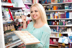 Satisfied positive female customer buying skin powder. In makeup section stock image