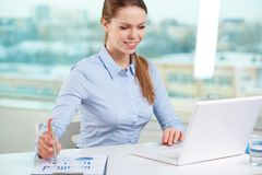 Satisfied with results. Lovely office girl being satisfied with financial results Royalty Free Stock Images
