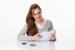 Satisfied 20s business girl working or studying at her desk Royalty Free Stock Image