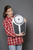 Satisfied 30s woman holding her weight scale for weight loss success Royalty Free Stock Photo