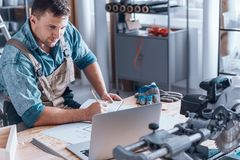 Satisfied self-employed engineer. Working at desk with laptop, metal parts and gloves Stock Photos