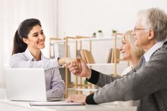 Satisfied senior couple making sale purchase deal. Handshaking real estate agent or realtor stock image