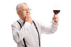 Satisfied senior gentleman tasting red wine Stock Photography