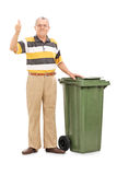 Satisfied senior standing by a trash can Royalty Free Stock Image