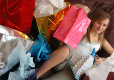 Satisfied shopper. A teen girl lying back on a couch with lots of shopping bags surrounding her Stock Photography
