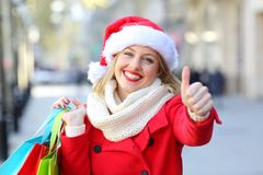 Satisfied shopper with thumbs up on christmas. Satisfied shopper hoolding shopping bags with thumbs up on christmas in the street stock photo