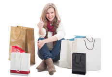 Satisfied shopping woman showing ok or thumb up. Sitting between shopping bags Stock Photo