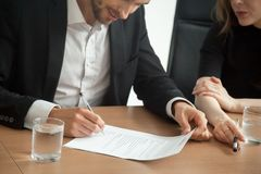 Satisfied smiling businessman in suit signing contract at meetin royalty free stock photo