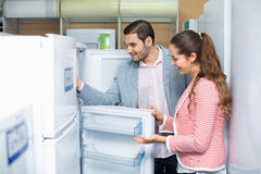 Satisfied  smiling couple looking at large fridges Stock Photos