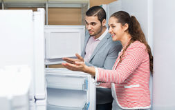 Satisfied  smiling couple looking at large fridges Royalty Free Stock Photo