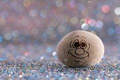 The satisfied stone emoji. Emotions on color glitter boke background royalty free stock images