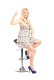 Satisfied stylish girl sitting on a modern chair Stock Images