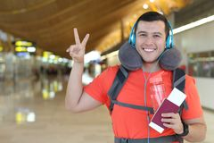 Satisfied traveler giving a peace sign from the airport stock images