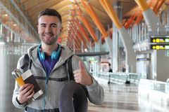 Satisfied traveler giving a thumbs up from the airport royalty free stock photo